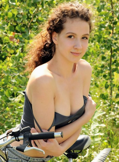 Curly Melissa Maz stripping by her bike
